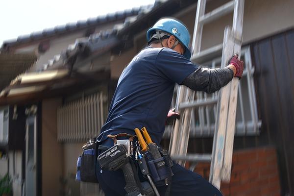 屋根に登ろうとする従業員