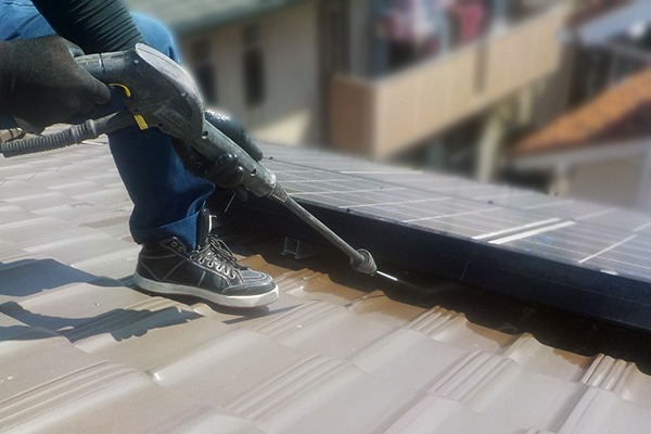 太陽光パネルの下にあるハトの巣やフンを高圧洗浄機で清掃します